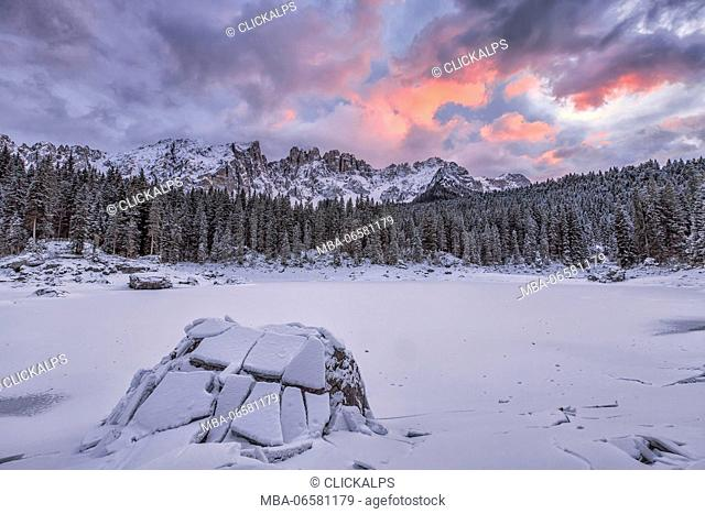 Sunset at Lake Carezza covered with snow in the background the Latemar group, Ega Valley, Dolomites, Trentino Alto Adige Italy