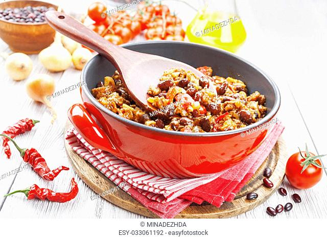 Chili con carne in the pot on a wooden table