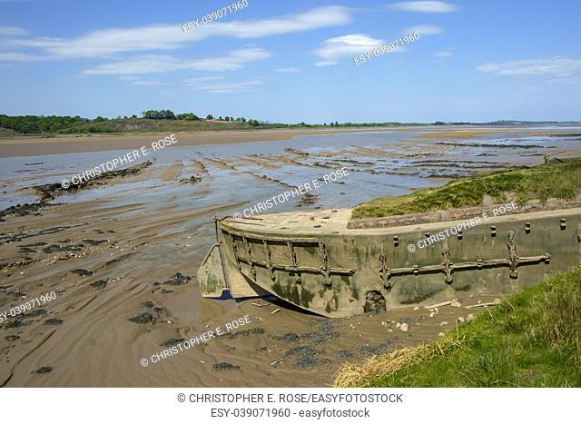 Obsolete small boats and barges were stranded on the banks of the tidal River Severn in Gloucestershire, UK to protect the river banks from erosion