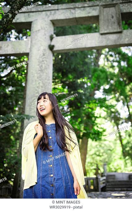 Smiling young woman wearing blue dress and yellow shirt at Shinto Sakurai Shrine, Fukuoka, Japan