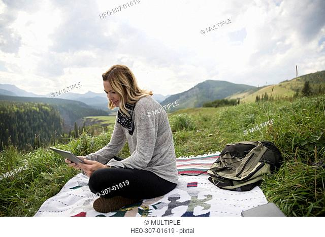 Woman using digital tablet on blanket in remote rural field