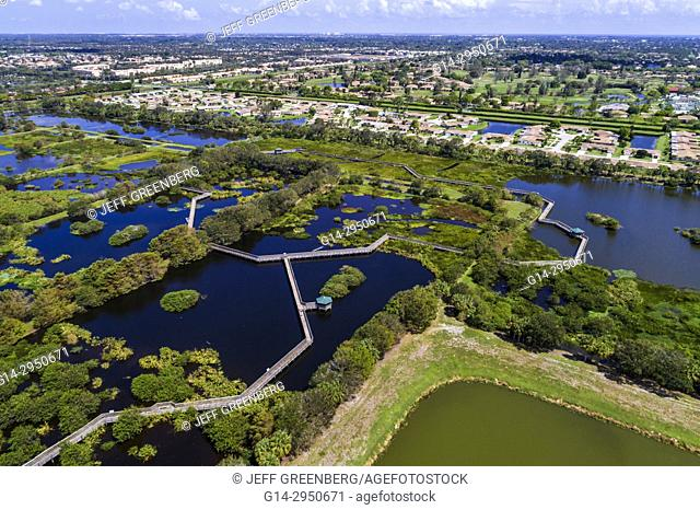 Florida, Delray Beach, Wakodahatchee Nature Wetlands, raised boardwalk trail, aerial overhead bird's eye view above, residential neighborhood houses homes