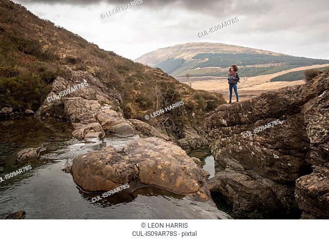 Woman standing on rocks, Fairy Pools, Isle of Skye, Hebrides, Scotland