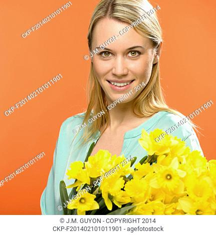 Spring woman hold yellow narcissus flowers on orange background