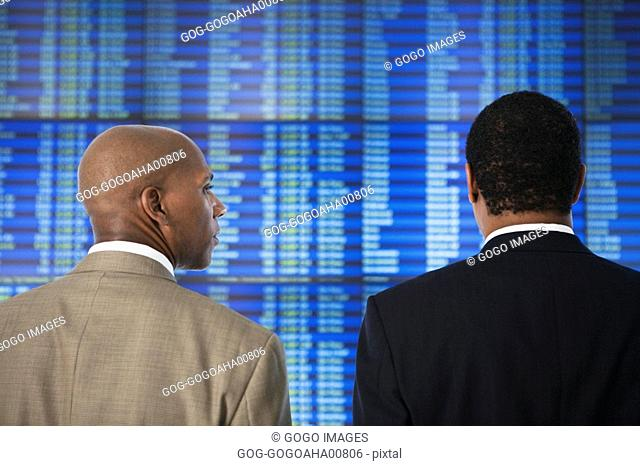 African businessmen in front of Arrival Departure board