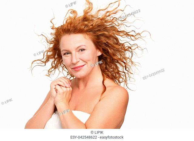 Portrait of sexy mature or middle aged woman smiling for camera. Beautiful lady posing for photographer isolated on white background