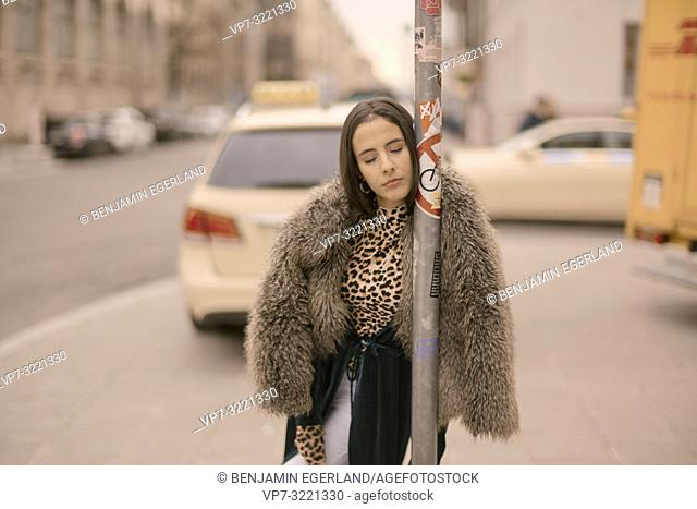 sensitive woman with closed eyes leaning on lamppost at street in city, exhausted mood, tired, sleepy, Munich, Germany