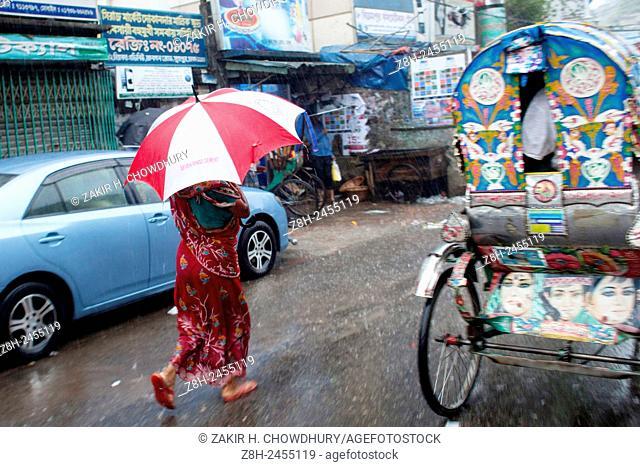 DHAKA, BANGLADESH - 11th June : An women walking on street using umbrella during rain in Dhaka on 11th June 2015