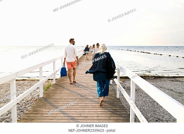 People walking on pier at seaside
