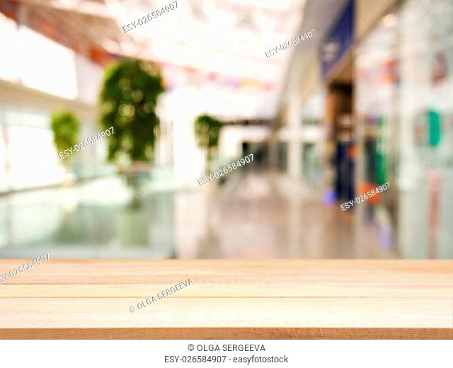 Wooden board empty table in front of blurred background. Perspective light wood over blur in shopping mall - can be used for display or montage your products
