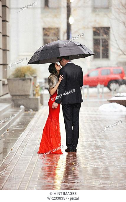 A woman in a long red evening dress with fishtail skirt and a fur stole, and a man in a suit kissing under an umbrella on a street