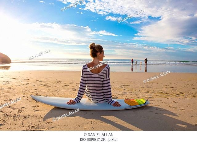 Female surfer sitting on surfboard at beach, rear view, Cape Town, Western Cape, South Africa