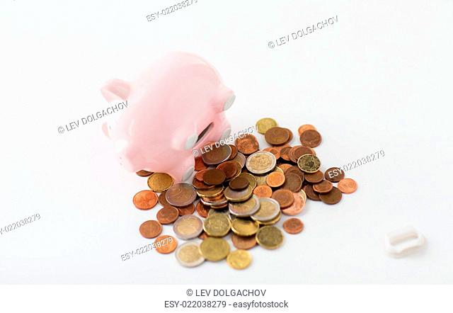 business, finance, investment, money saving and budget concept - close up of euro coins and piggy bank on table