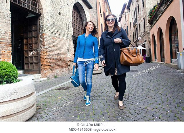 Two women walking in the streets of the city. Treviso (Italy) 4th april 2014