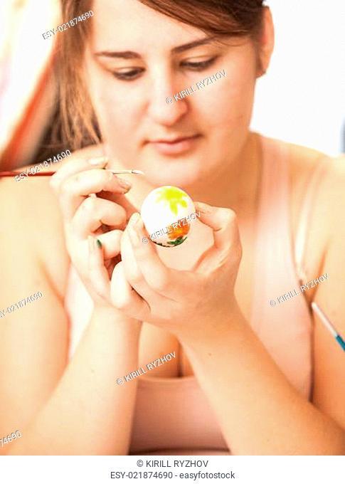 Brunette woman painting white easter egg