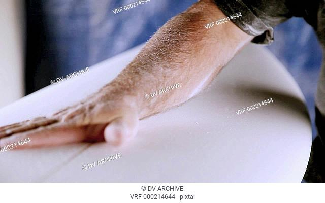 A man works on building a surfboard