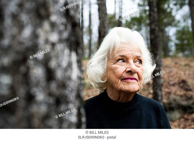 Portrait of senior woman looking away in forest