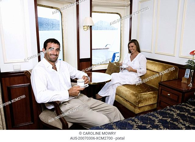 Mid adult couple drinking tea in a cabin of a sailing ship and smiling