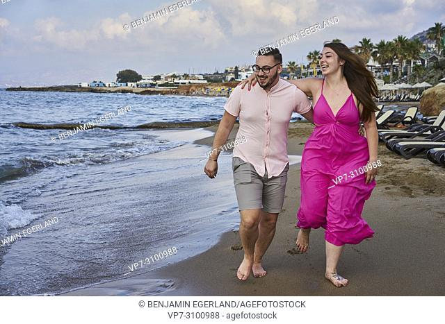 Chersonissos, Crete, Greece, couple walking on beach, playful, fun, holiday, relationship