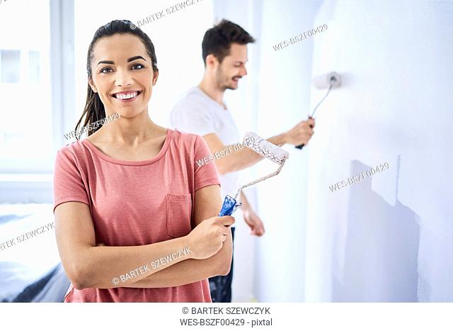 Portrait of happy woman painting wall with boyfriend in new apartment