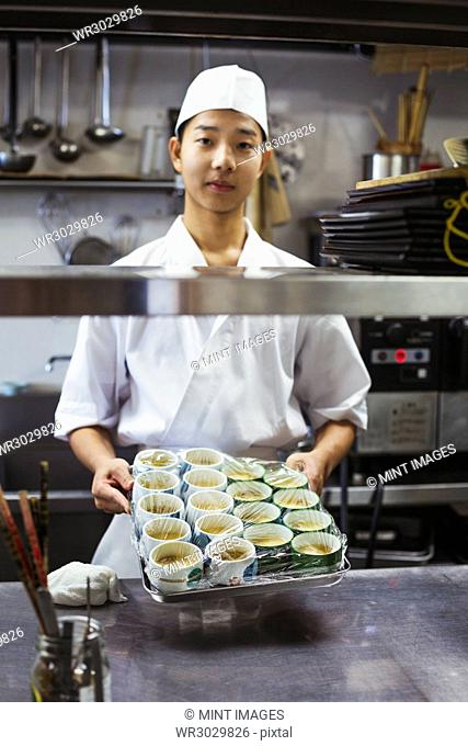 Chef working in the kitchen of a Japanese sushi restaurant, holding tray with small bowls of food