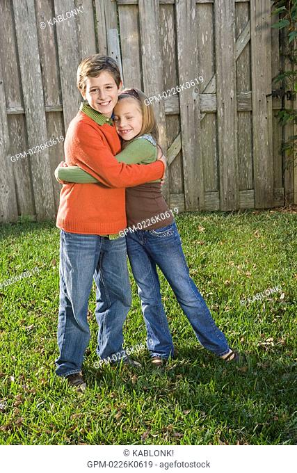 Portrait of young boy and young girl hugging in front of backyard fence, looking at camera