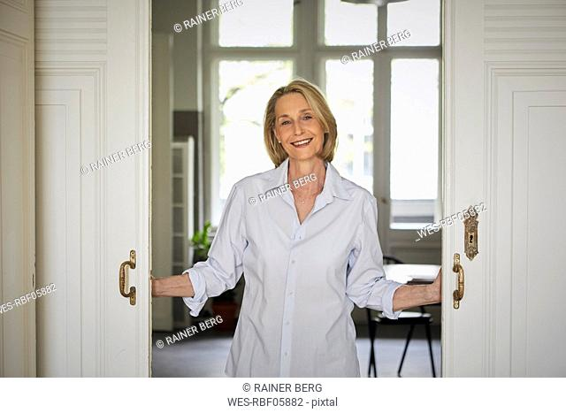 Portait of smiling mature woman opening door at home