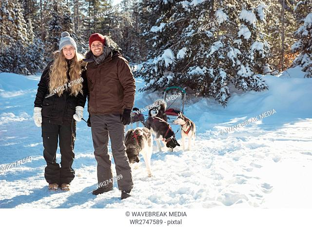 Portrait of smiling mushers standing with sledge