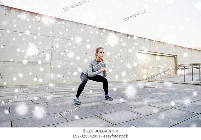 fitness, sport, exercising and healthy lifestyle concept - woman doing squats outdoors over snow
