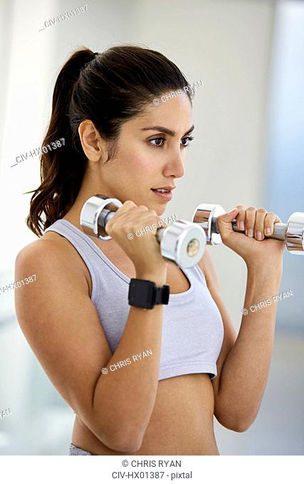 Focused brunette woman doing biceps hammer curls with dumbbells
