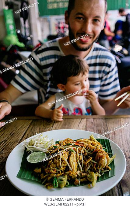 Thailand, Father and daughter eating delicious pad thai dish on a street restaurant