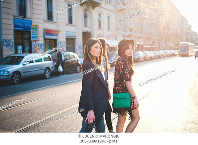 Three young women strolling on city road
