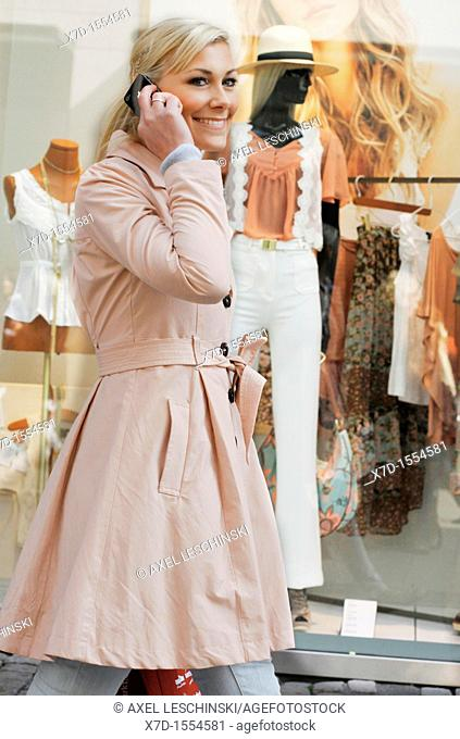 woman is shopping in the city and take a call on a cell phone