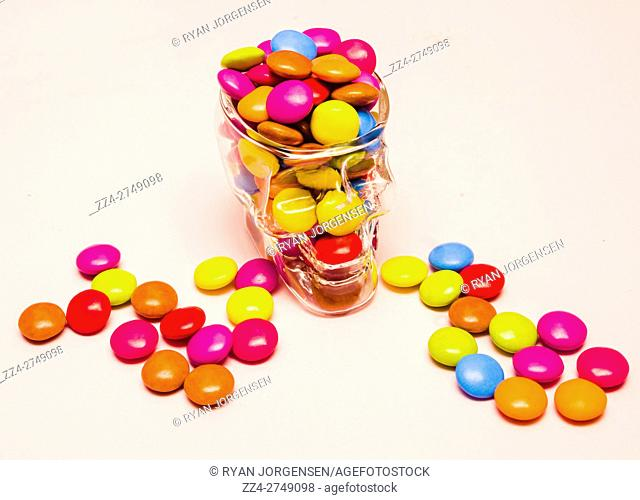 Colourful halloween horror lollies overloaded inside the glass of sugar skull candy jar. Holiday candies