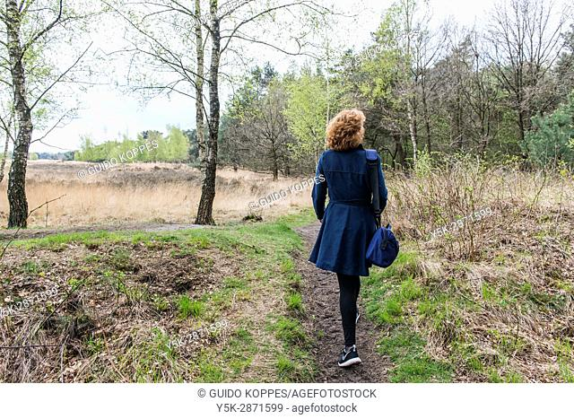 Regte Heide, Riel, Netherlands. Red headed caucasian woman strolling a nature reserve park and forest on a free weekend afternoon