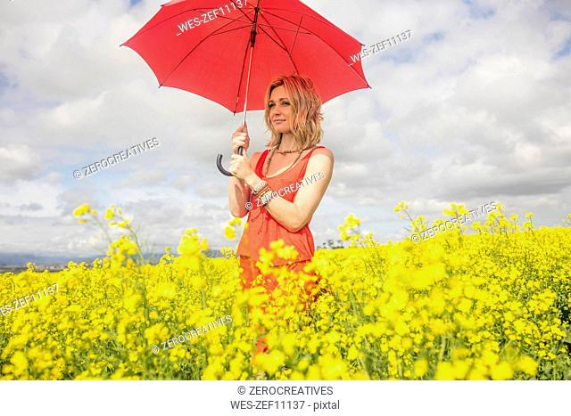 Blond young woman wearing red dress standing in rape field holding red umbrella