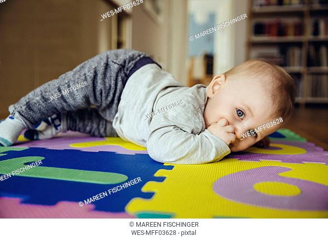 Portrait of baby boy with finger in his mouth lying on the floor in the living room