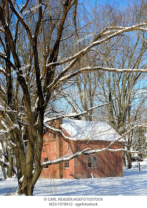 The sky has cleared at dawn after the night dumped a coating of snow on a small red barn, Pennsylvania, USA