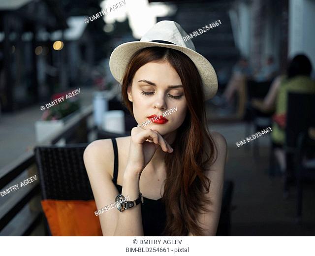 Pensive Caucasian woman at sidewalk cafe