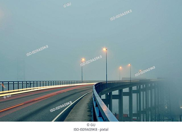 Diminishing perspective of light trails on misty elevated road illuminated by street lights, Haugesund, Rogaland County, Norway