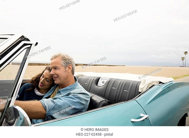 Affectionate couple riding in convertible along beach