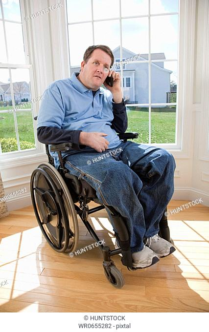 Man with spinal cord injury in a wheelchair talking on a mobile phone