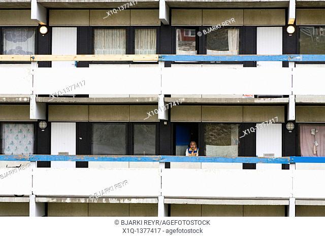 Man looking out from his window, residental apartments  Qaqortoq Julianehåb, South Greenland