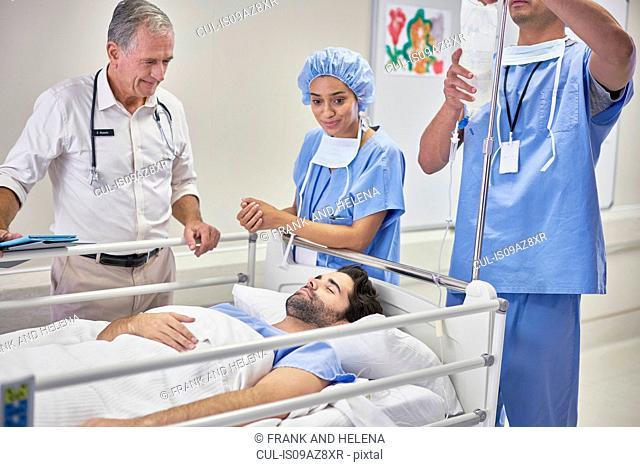 Doctors surrounding patient in hospital bed