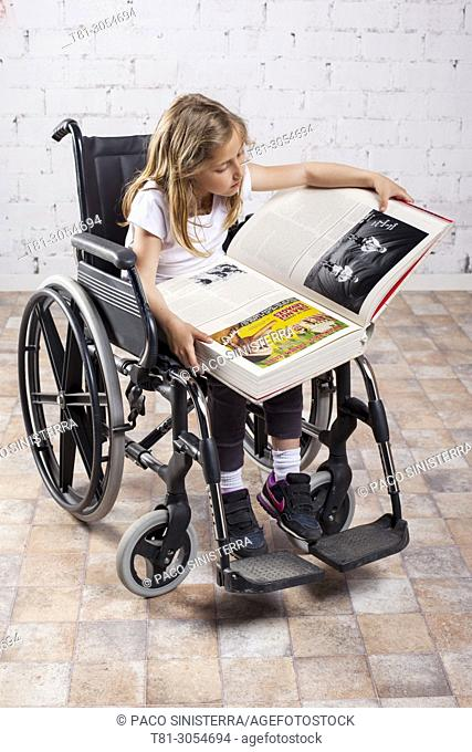 girl in wheelchair reading in waiting room, Valencia, Spain