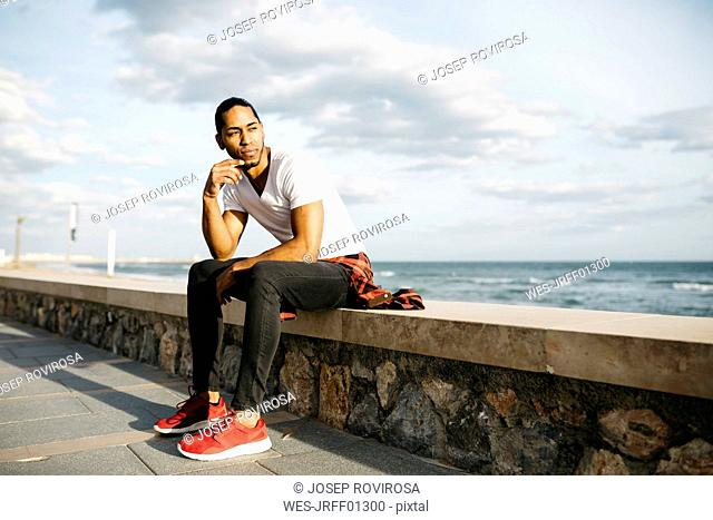 Young man sitting on wall at beach promenade looking at distance
