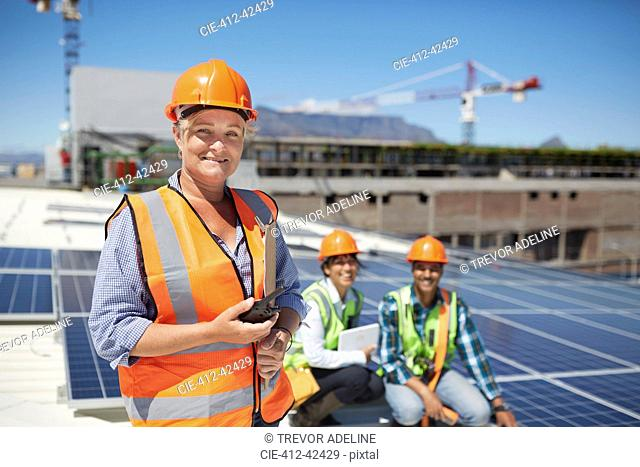 Portrait smiling, confident female engineer with walkie-talkie at sunny solar power plant
