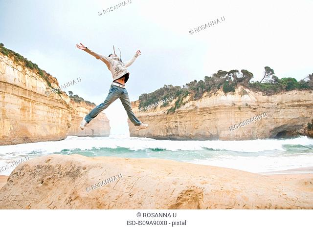 Young man jumping by Loch Ard Gorge, Melbourne, Australia