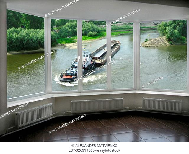 plastic window with view of barge going on the river