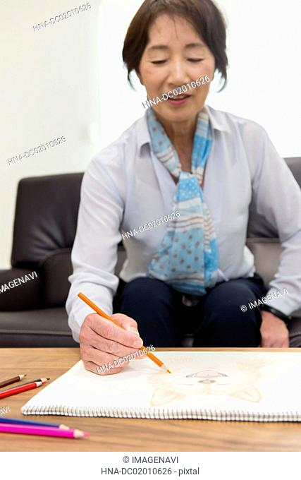 A senior woman painting a picture